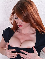 Redhead Molly Gingham unleashes her firm fake breasts.