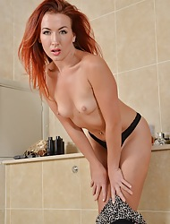 MILF Redhead Jazz fingers her pussy in transmitted to bathroom.